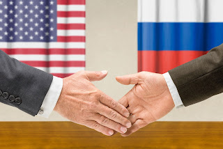 Diplomats touch hands in front of US and Russian flags,