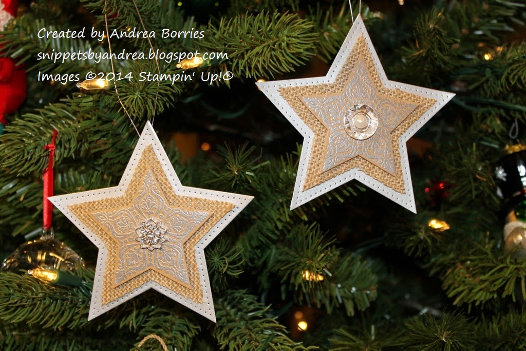 Two star-shaped Christmas ornaments made with layers of silver paper, burlap and stamped kraft paper.