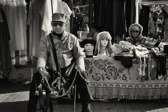 An eccentrically dressed vendor next to his stall creates a surreal street photograph