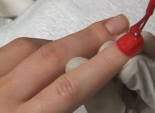 passando esmalte vermelho nas unhas