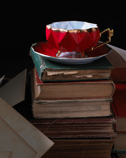red tea cup and saucer on top of four old books