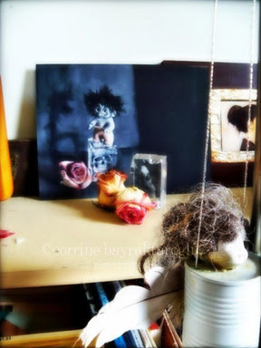 troll painting with dried roses on studio shelf