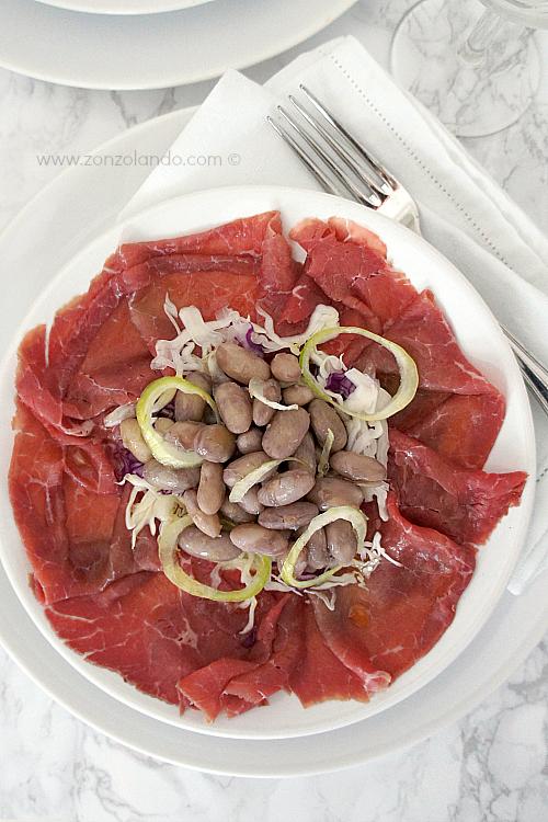 Carpaccio di carne salada salata e fagioli ricetta tipica trentina - row salted beef carpaccio typical italian recipe