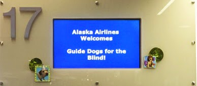 "Blue digital sign that reads ""Alaska Airlines Welcomes Guide Dogs for the Blind!"""