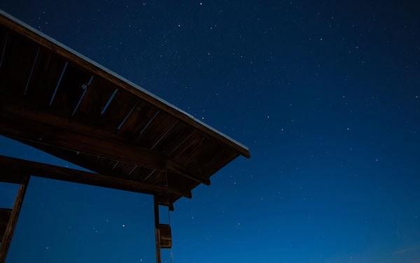 art house in desert reflecting stars in mirror siding