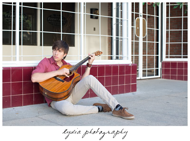 Senior playing guitar in front of a shop at Forest Lake Christian senior lifestyle portraits in Rocklin, California