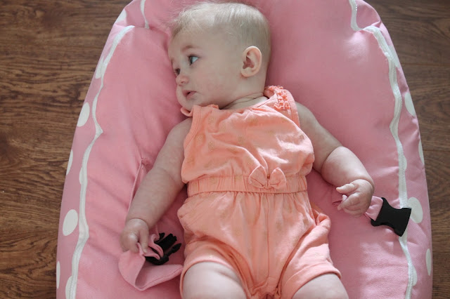 baby girl on pink bean bag wearing peach playsuit with gold glitter butterflies and bow at waist