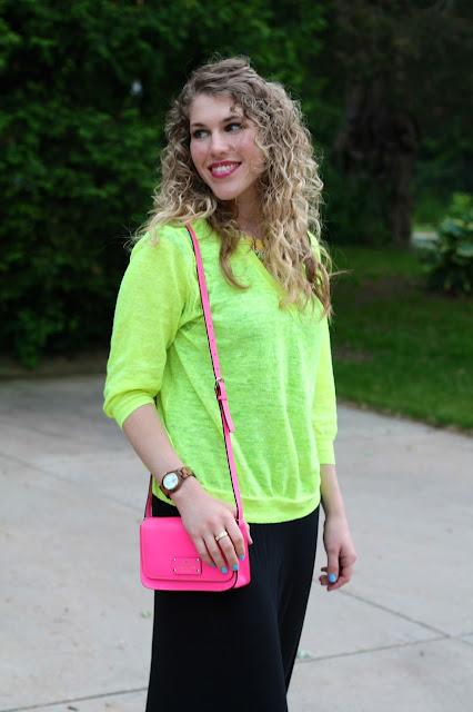 black maxi dress, neon yellow sweater, pink crossbody Kate Spade bag
