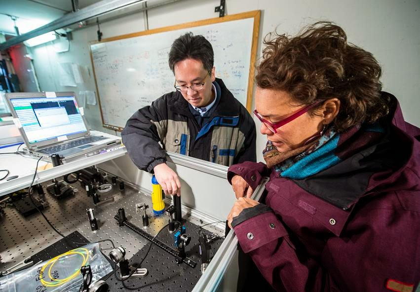 Fermilab scientist Aaron Chou, left, project manager for the Holometer experiment, and Vanderbilt University graduate student Brittany Kamai peer into the device that will test whether the universe is a 2-D hologram. Credit: Fermilab.