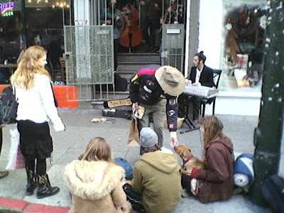A woman leans over to pet a dog in the lap of one of three audience members seated on the sidewalk.