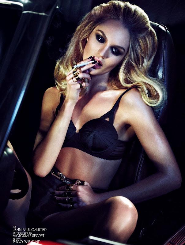 Candice Swanepoel in a black bra smoking a cigarette