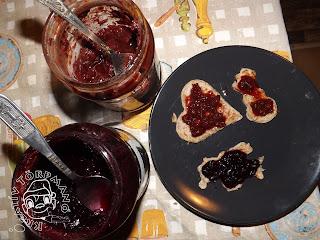 Szöveg: Névnapi finomság: ribizlis és meggydzsemmes formás palacsinták! Kép: Asztali felülnézet. A terítőn két dzsemmes üveg, melyekben egy-egy kanál van, az üvegek mellett meg a szürkés-fekete tányéron rajta lévő három dzsemmes formás palacsinta.