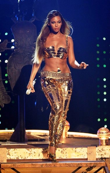 Fashionista and singer Beyonce glamorous style outfits gold sultry goddess outfit in concert.
