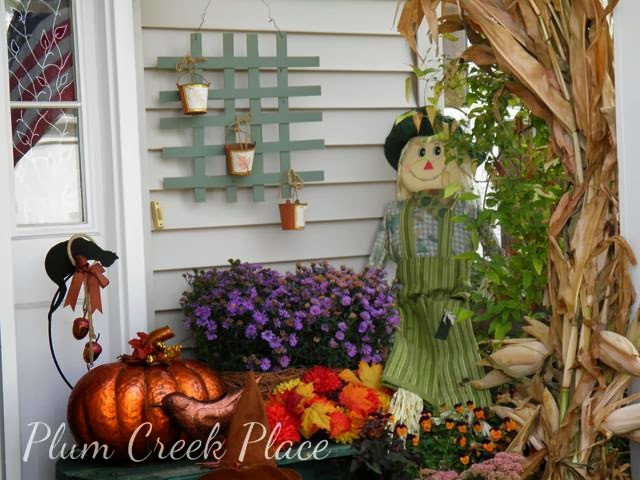 fall porch decoration, cornstalks, mums, scarecrow