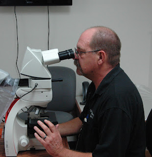 Dr. Veasey uses a microscope to evaluate suspicious deaths for contagious diseases.
