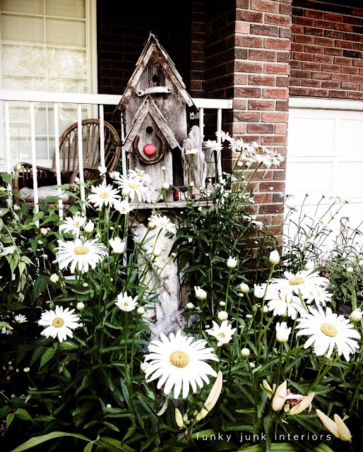 old wood birdhouses in a bed of daisies