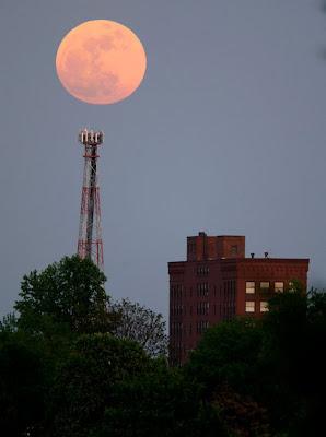 la superluna sobre una antena y edificios en los estados unidos