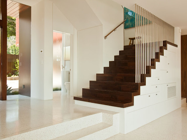 Picture of dark brown wooden staircase on the white concrete wall in the hallway