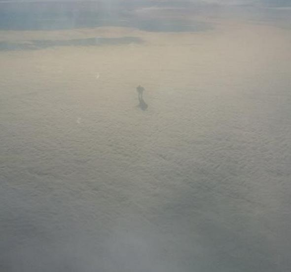 A plane passenger spotted a mysterious figure walking on the clouds 30,000 ft. above the ground.