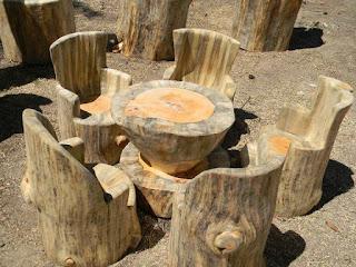 Living con sillas y mesa hecho con troncos