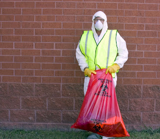 Man in biohazard suit holds bag of hazardous material.