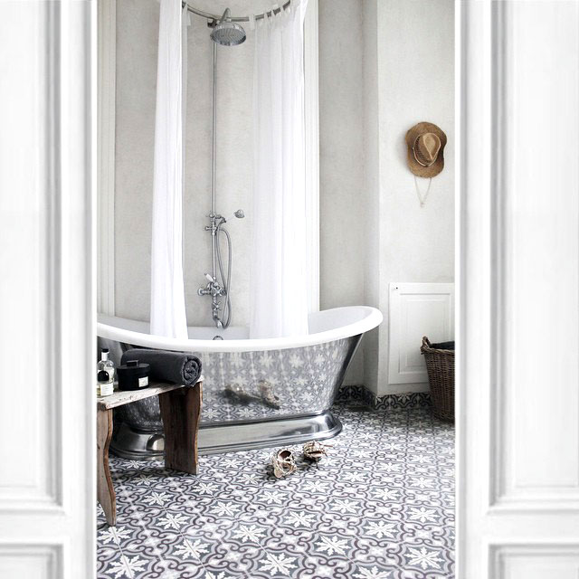 Mirrored freestanding tub in a bathroom with Moroccan inspired tile