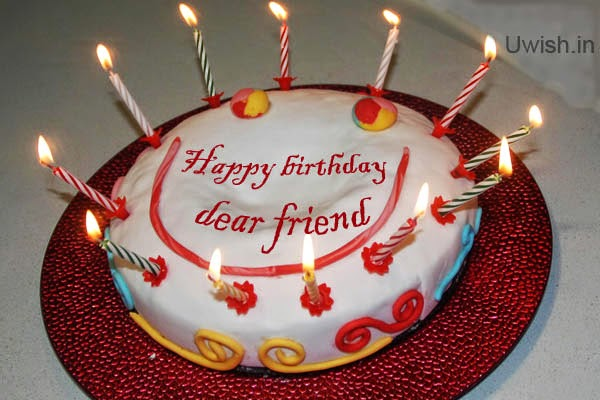 Happy Birthday dear friend e greetings and wishes with smile on cake.