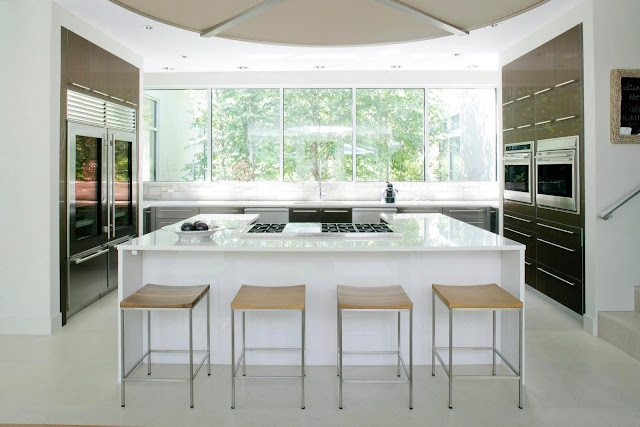 White kitchen in a modern farmhouse with wooden cabinets with long drawer pulls, a large white island and a large window