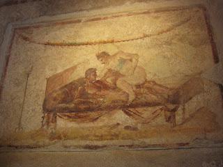 Fresco above a doorway inside a Pompeii brothel.