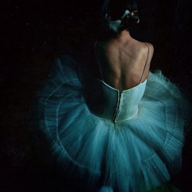 ballerina sitting on the floor in darkness