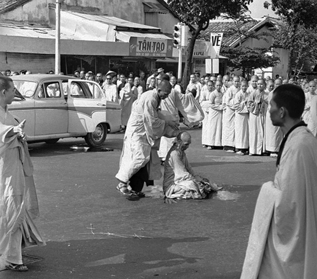 Thich Quang Duc is doused with gasoline while calmly sitting down in the traditional Buddhist meditative lotus position.
