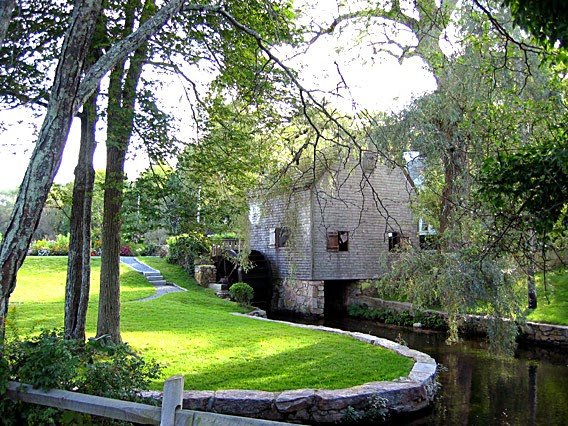 wood shingled mill bulding with willow trees, stone wall, and flowing water.