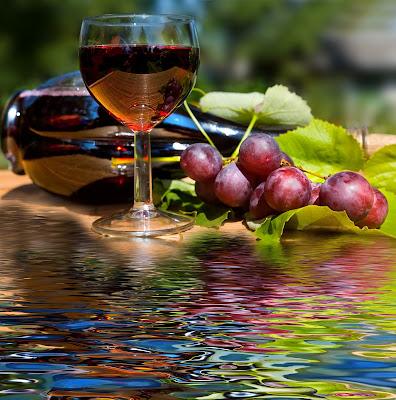 Vino tinto y copa servida que incluyen un delicioso racimo de uvas globo