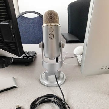 Picture of the Yeti microphone in between the PC and the Mac