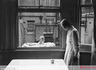 Criança dentro de uma gaiola, vigiada por uma mulher
