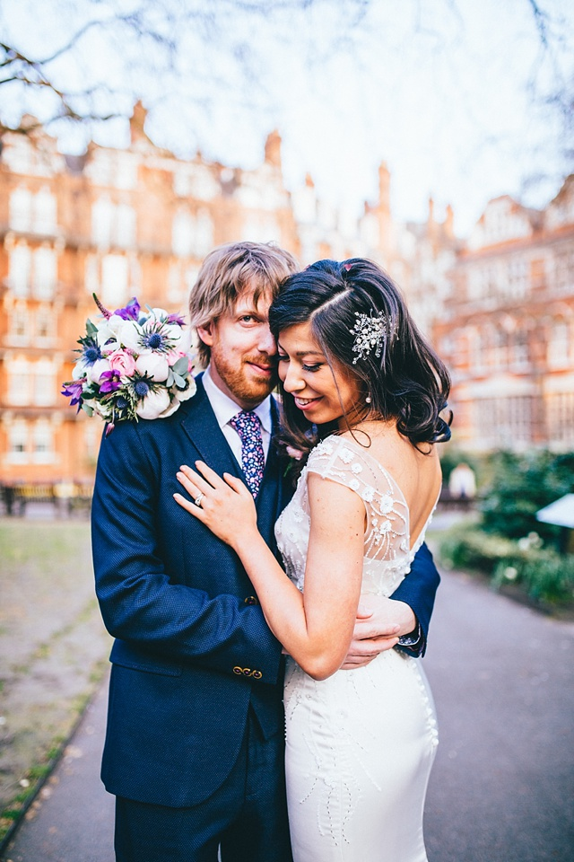 beautiful couples portrait of bride and groom hugging in central london near mayfair library