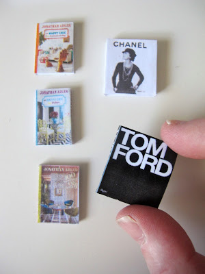 Selection of five modern dolls' house miniature books on design, one of which is being held between a finger and a thumb.