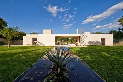 Fachada de moderna casa hacienda con estanque
