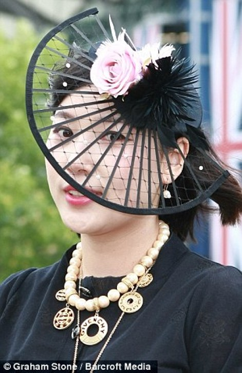 pretty lady in a fan shaped hat enlivened with a pink silk rose on day 2 at Royal Ascot, 2014