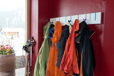 mounted coat rack with coats on a red wall
