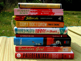 Book pile: The Pirates in an Adventure with Scientists by Gideon Defoe, Forest Born by Shannon Hale, Yellowcake by Margo Lanagan, Pirate Cinema by Cory Doctorow, Binny for Short by Hilary McKay, Disturbed by Her Song by Tanith Lee, Was… by Geoff Ryman, Bachelor Girl by Betsy Israel, Paleofantasy by Marlene Zuk