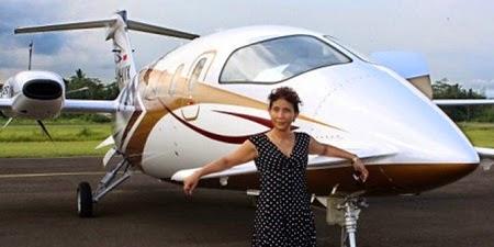 Foto gambar Susi pudjiastuti di depan Pesawat pribadinya