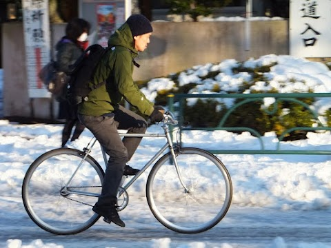 A cyclist challenges snowy road conditions in Tokyo.