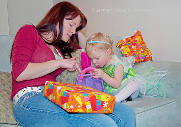 Mom Helps Toddler Girl Open Birthday Gifts This Young Mother Is Helping Her Cute 2 Year Old Caucasian Daughter Presents
