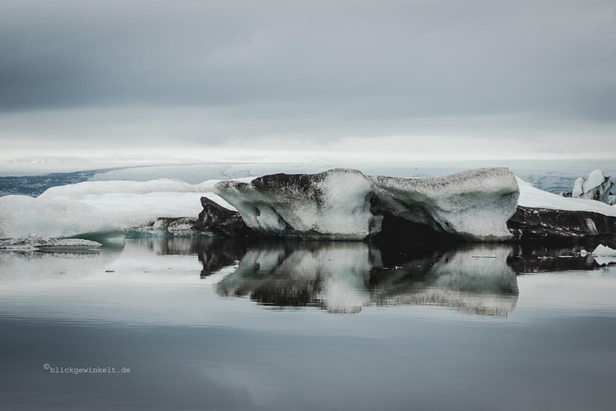 Eisberg spiegelt auf stillem Wasser