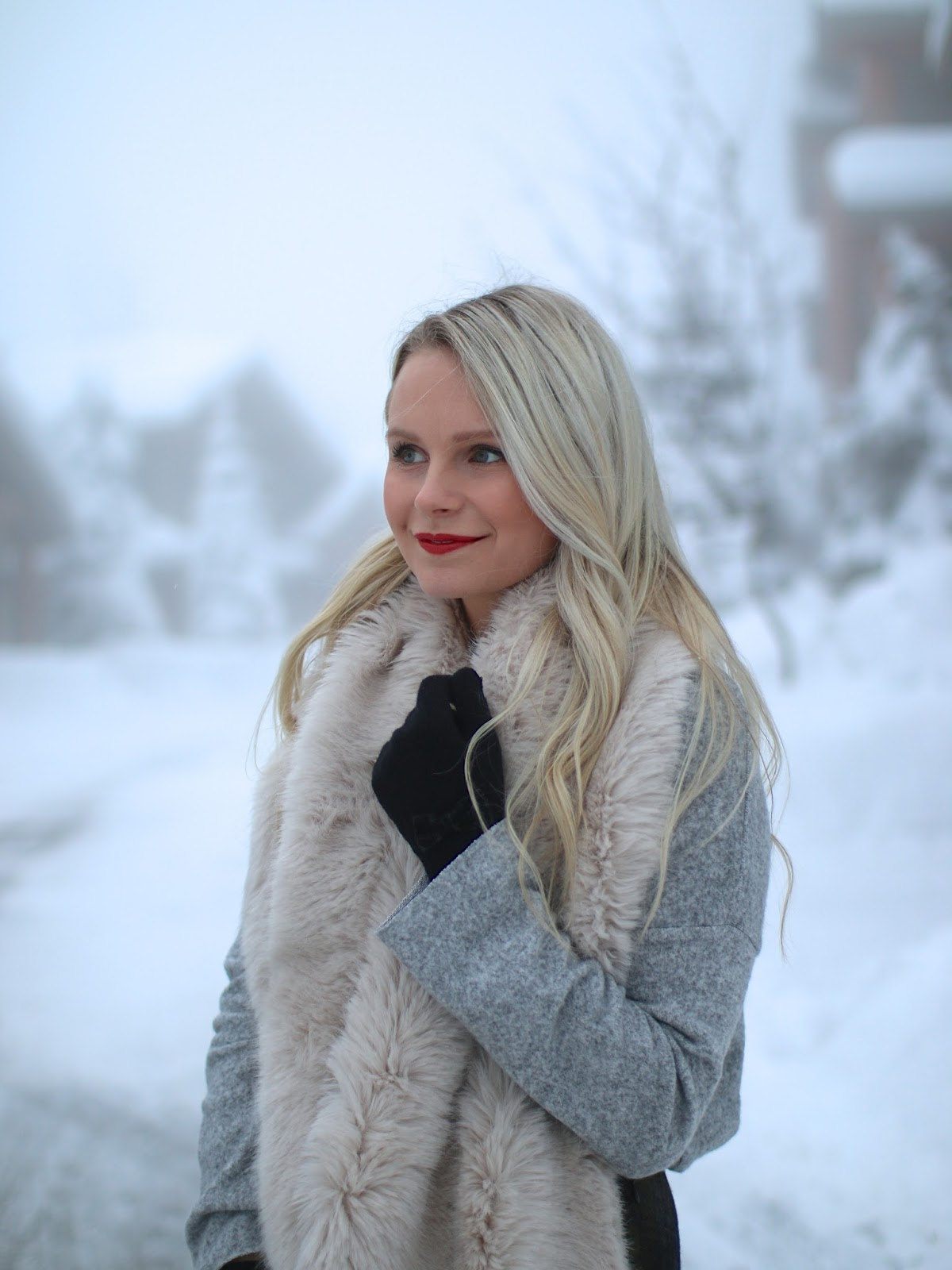 girly outfit and red lips in the snow during the holidays
