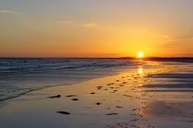 Amanecer en la playa con huellas sobre la arena