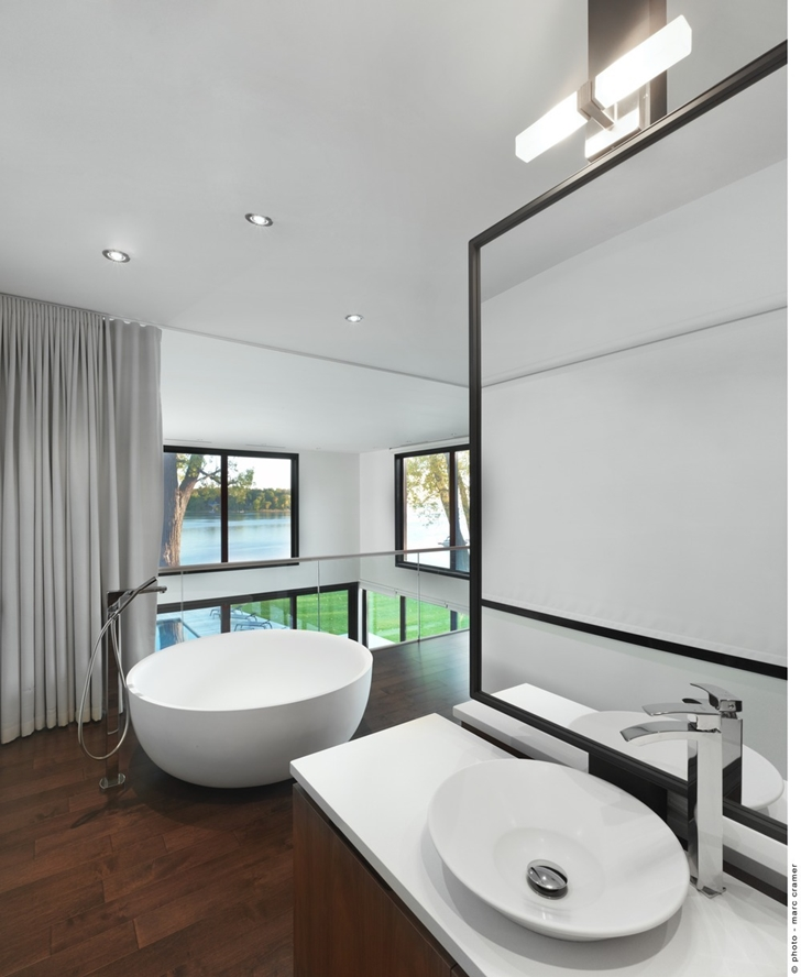 Modern bathroom in Renovated Bord-du-Lac House by Henri Cleinge