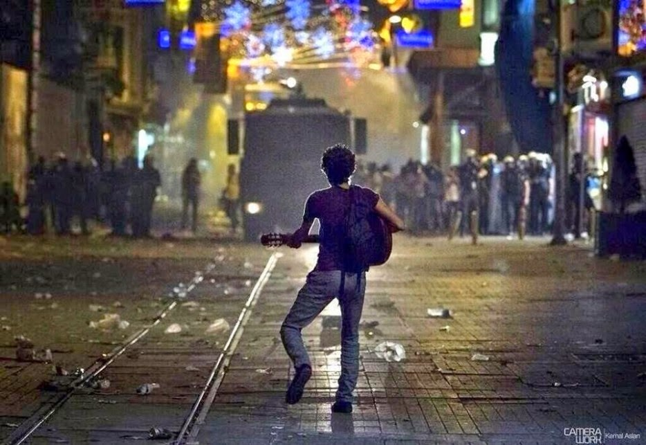 35 moments of violence that brought out incredible human compassion - a turkish protestor plays guitar for police