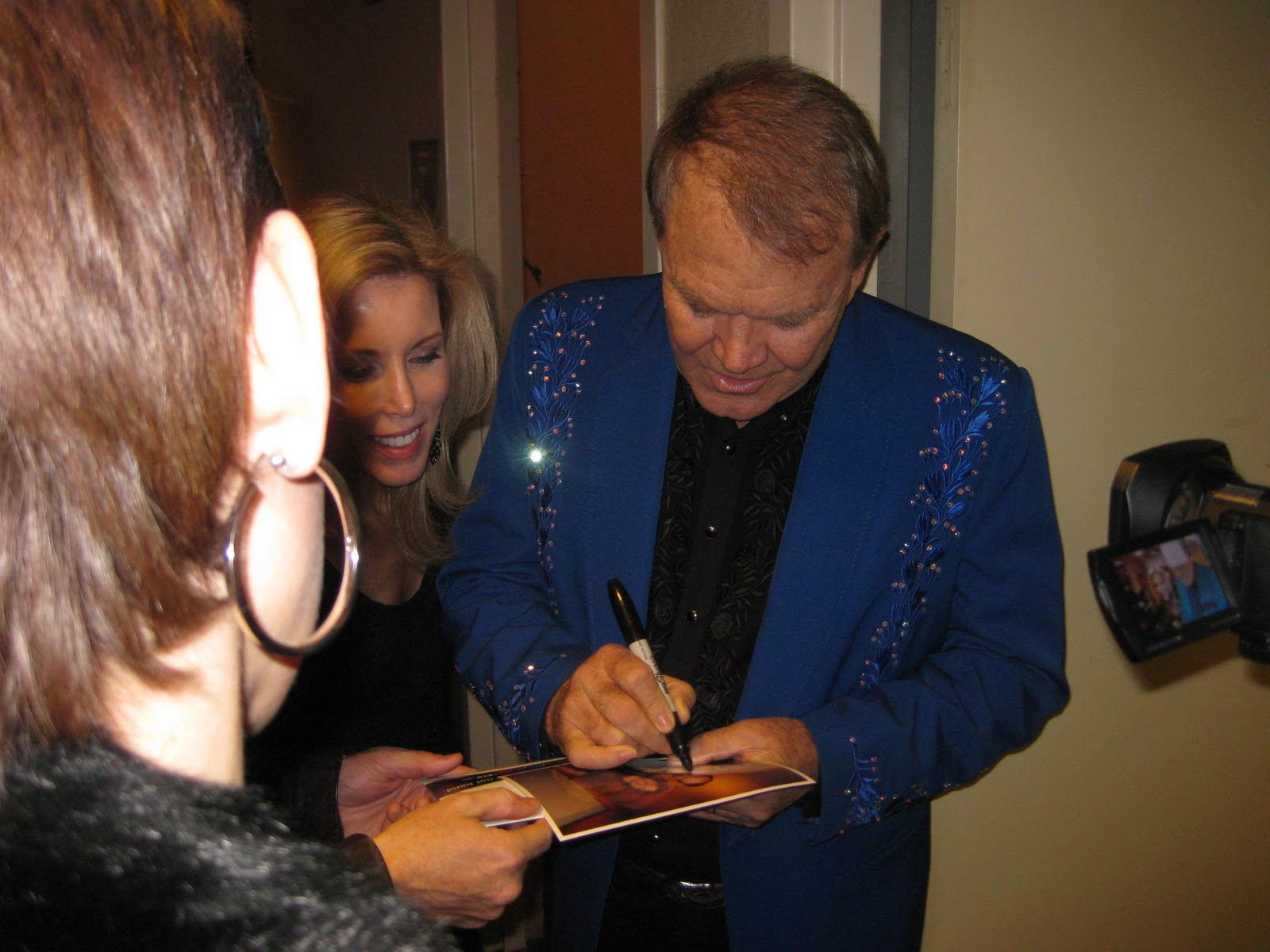 Glen signs robert s photo his wife kim looks on
